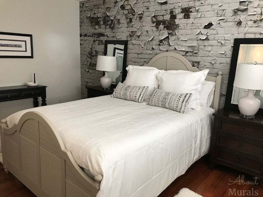 A white brick wallpaper with peeling paint on the wall in a bedroom from AboutMurals.ca