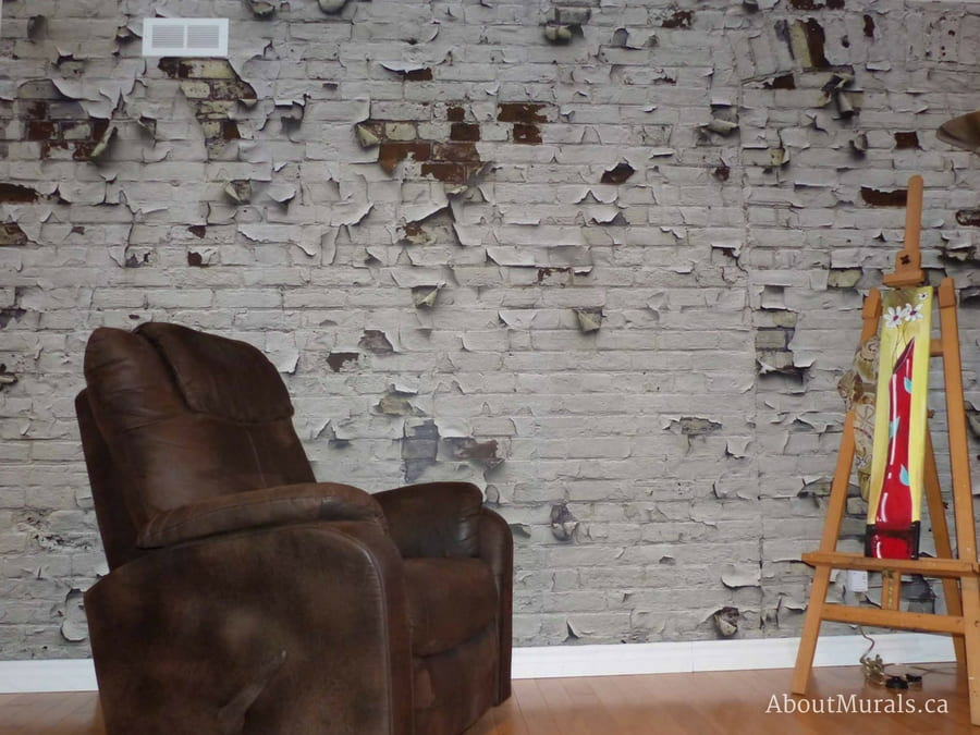 An industrial brick wallpaper with white peeling paint in an artist loft. Sold by AboutMurals.ca
