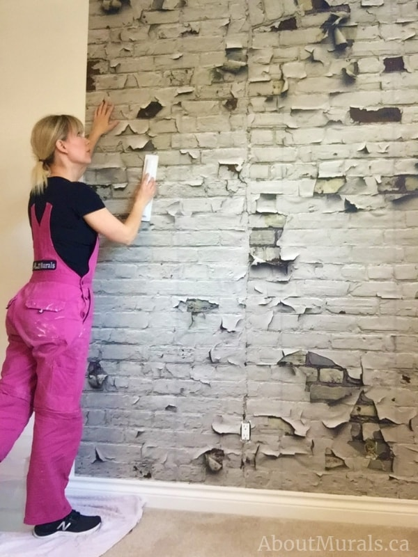 A wallpaper installer hangs a faux brick wallpaper