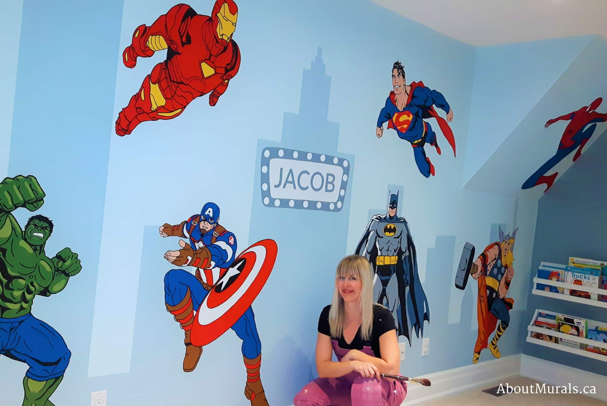 Mural painter Adrienne Scanlan sits next to a kids wall mural she painted featuring the Hulk, Captain America, Batman, Superman, Spiderman, Thor and Captain America