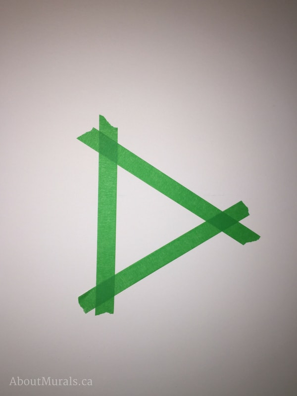 A triangular stencil made from green painters tape by muralist Adrienne of AboutMurals.ca