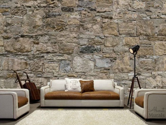 Castle Stone Wallpaper, as seen in a living room, features a wall of brown rugged rocks. Easy wallpaper sold by AboutMurals.ca.