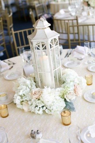 lantern-wedding-centerpiece-white-wooden-lantern-with-a-candle-surrounded-by-white-flowers-and-ruddy-roses-on-the-wedding-table-millimeter-photo-via-instagram-334x500