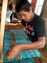 Young man weaving a wide piece of cloth