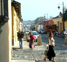 Woman carrying firewood on her head on the cobblestone street