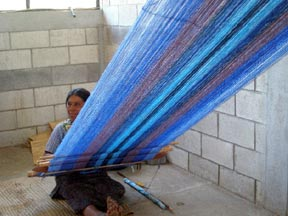 Woman weaving a wide backstrap fabric