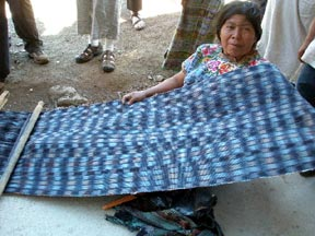 A woman proudly displays the wide jaspé fabric she has woven on a backstrap loom