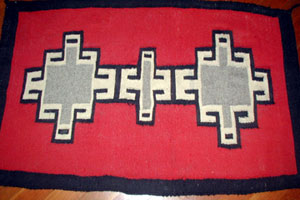 A Ganado-style rug in black, gray, and white with a red background and a black border