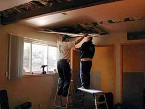 Two men lift a panel of wallboard to the ceiling