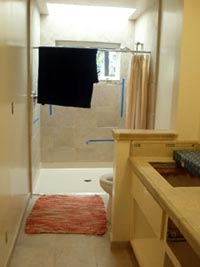 Bathroom with towel hanging on temporary shower curtain rod and with rug on the floor