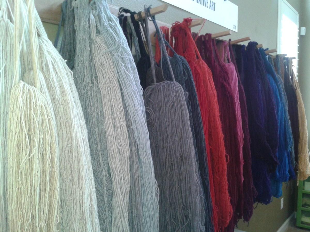 Yarns hanging behind the looms,