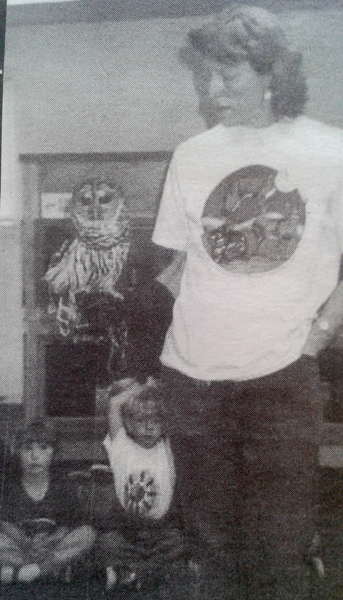Photo of Dorothy Johnson holding a hawk as students watch