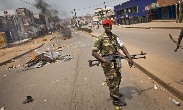 A heavily armed military policeman patrols next to burning barricades set up by angry supporters of opposition leader Kizza Besigye, near to his party headquarters, in Kampala, Uganda, Friday, Feb. 19, 2016. Police in Uganda arrested opposition leader Kizza Besigye at his party's headquarters Friday after heavily armed police surrounded the building and fired tear gas and stun grenades at his supporters who took to the streets. (AP Photo/Ben Curtis)