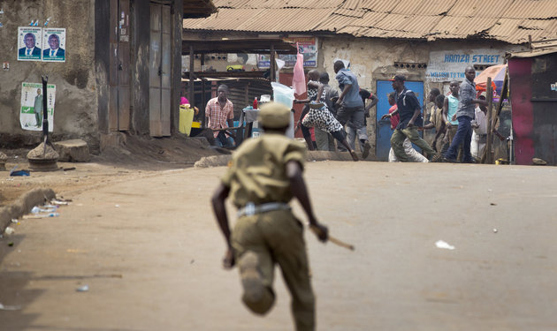 A policeman chases angry supporters of opposition leader Kizza Besigye, near to his party headquarters, in Kampala, Uganda Friday, Feb. 19, 2016. Police in Uganda arrested opposition leader Kizza Besigye at his party's headquarters Friday after heavily armed police surrounded the building and fired tear gas and stun grenades at his supporters who took to the streets. (AP Photo/Ben Curtis)