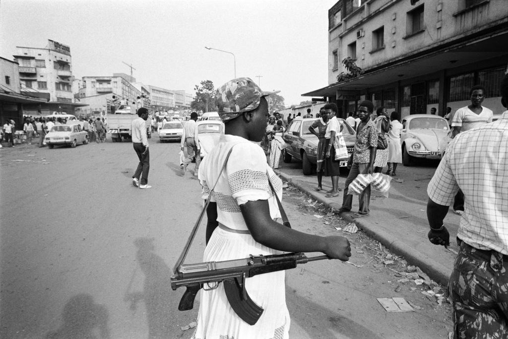 "National Resistance Army young girl soldier poses with her kalashnikov, on January 1986 in Kampala. The children soldiers of the NRA are mostly orphans whose parents were killed during the Obote regimes killing excesses. They are reputedly to be among the best and bravest fighters of Museveni's guerilla force. The NRA rebellion, lead by Yoweri Museveni took power 26 January 1986, after five years of fighting against the second Obote regime, popularly known as ""Obote II"", and its armed forces, the Uganda National Liberation Army (UNLA). (Photo credit should read ALEXANDER JOE/AFP/Getty Images)"