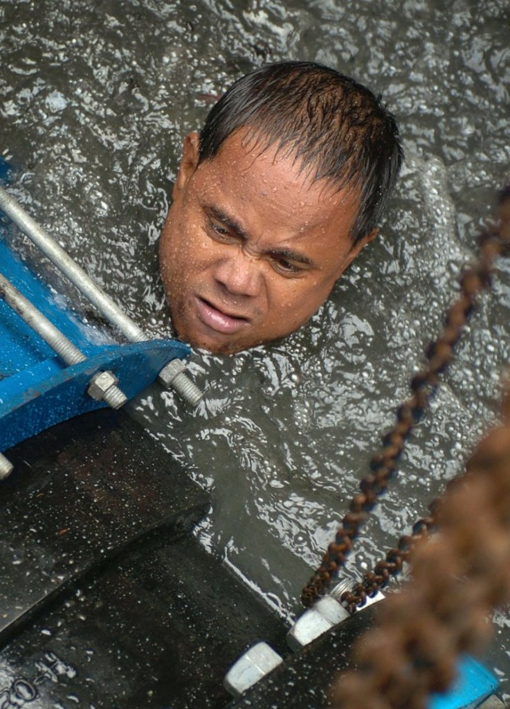 5 November 2004: A worker from the Maynilad Water utilities struggles to install a valve underwater on an excavated Manila's main water line as part of an upgrade of the water distribution systemRomeo Gacad/ AFP