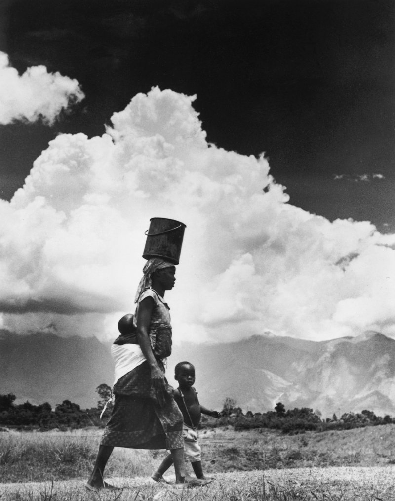 1955: A Rhodesian woman carries her baby on her back and a pail of water on her headGetty Images
