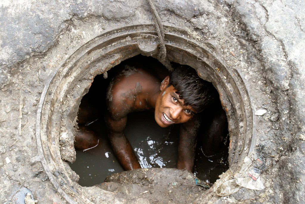 25 April 2007: A labourer cleans an underground sewage in DhakaRafiqur Rahman/ Reuters