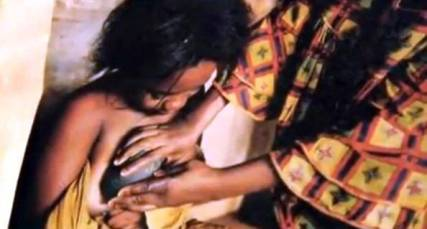 """YAOUNDE, CAMEROON - JUNE 22: A video grab of a woman """"ironing' her daughters breasts in an effort to stop them growing. A group of young mums are speaking out about a terrible painful ritual being carried out on young girls in Cameroon. 'Breast Ironing' is done on girls as young as six, and involves their chests being pressed with burning rocks and blunted knives. The """"traditional"""" practice aims to stop breasts from growing, but leaves the girls crippled, scarred and in agony. Parents believe that if girls develop too young, they will become promiscuous and fall pregnant, or get raped by men. (Photo by Barcroft Media / Getty Images)"""