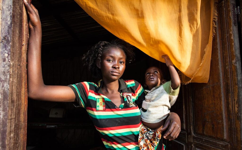 Bangui, CAR- Rosine Mengue, 18, holds her 1-year-old son in her home in the Castors neighborhood in Bangui, Central African Republic on Sunday, February 14, 2016. She says she was 16 when a Moroccan peacekeeper coerced her into sex for money, paying her a total of $8 for two visits and making her pregnant. (Jane Hahn for the Washington Post)