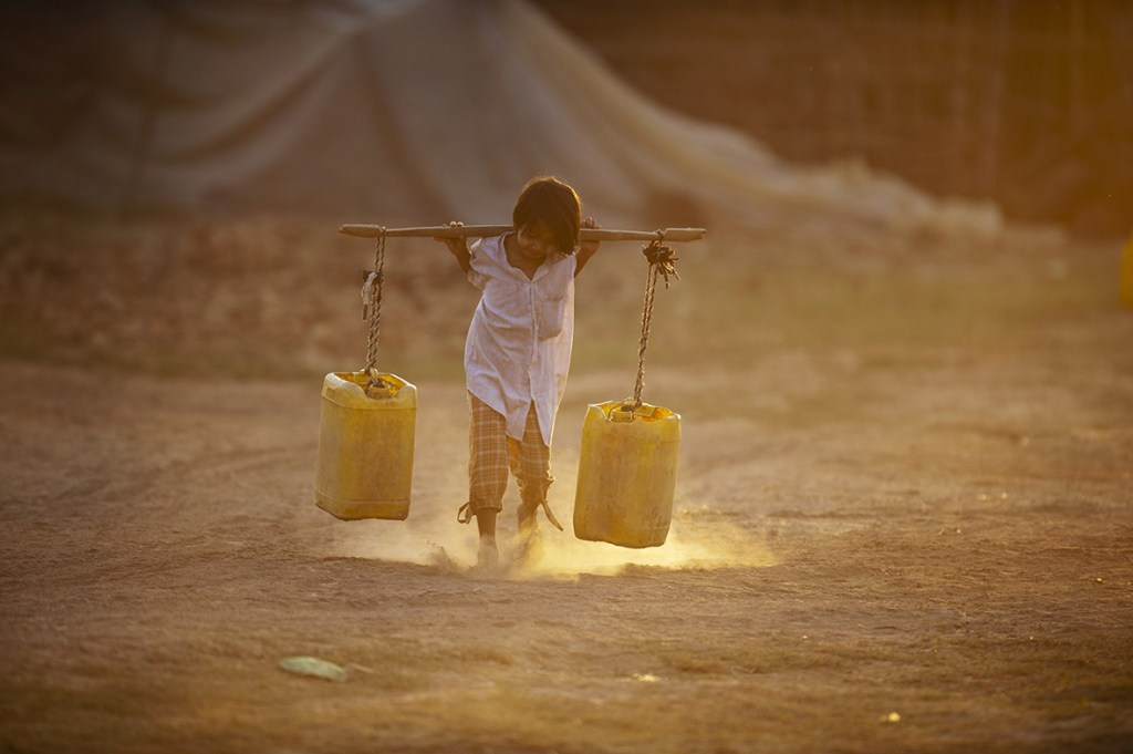 A child carries water home through a brick factory on the outskirts of Yangon Myanmar once known as the 'rice bowl of Asia' because of its agricultural richesYe Aung Thu/ AFP