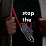 "A man shows the logo of a T-shirt that reads ""Stop the Cut"" referring to Female Genital Mutilation (FGM) during a social event advocating against harmful practices such as FGM at the Imbirikani Girls High School in Imbirikani, Kenya, April 21, 2016. REUTERS/Siegfried Modola"