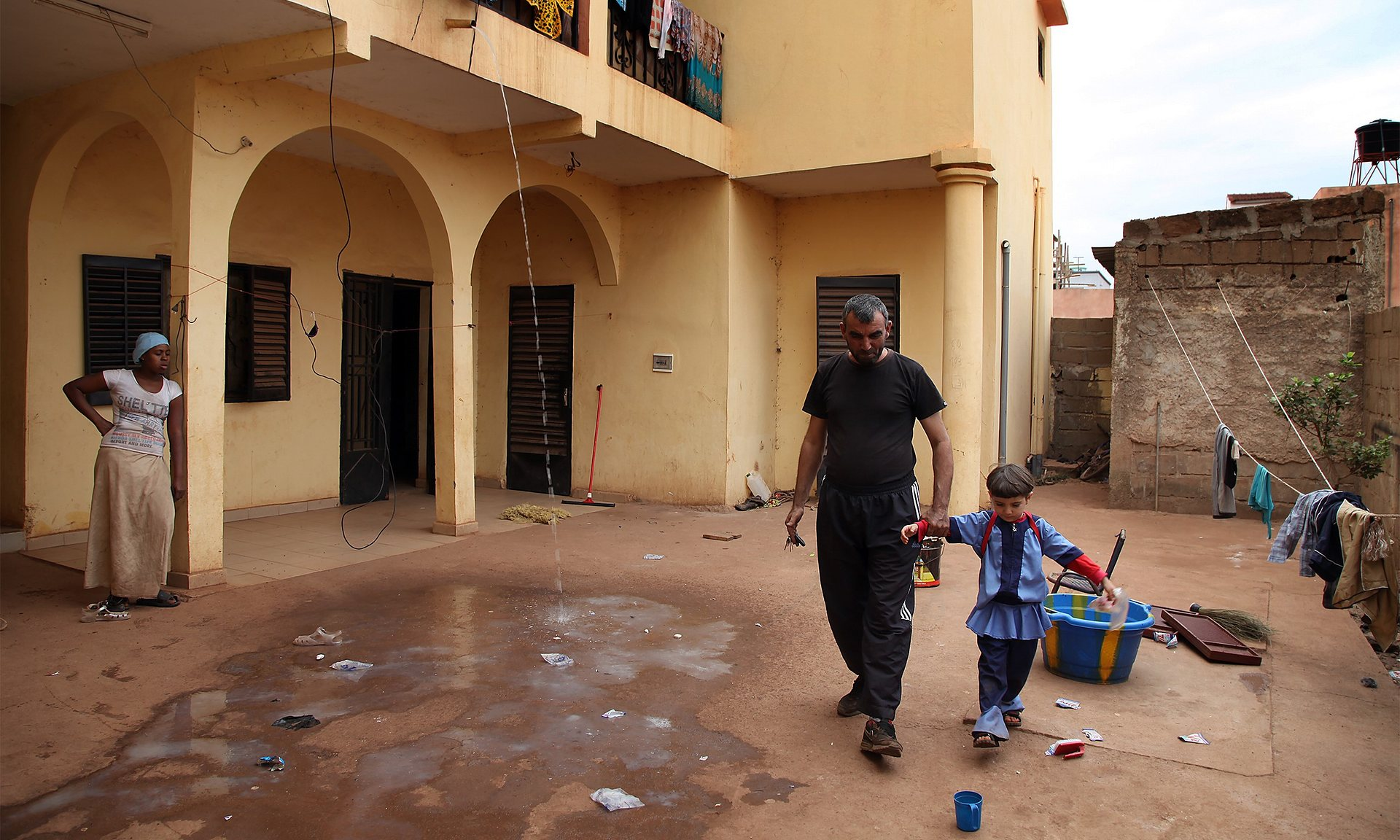 Cemal Ahmed, a 40-year-old refugee from the civil war in Syria, plays with his daughter at their apartment block in Bamako. Photograph: Baba Ahmed/Getty Images