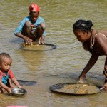 Children and a woman pan for gold in the river near the Madagascan city of Mananjary, June 2015. Photograph: Joerg Boethling/Alamy