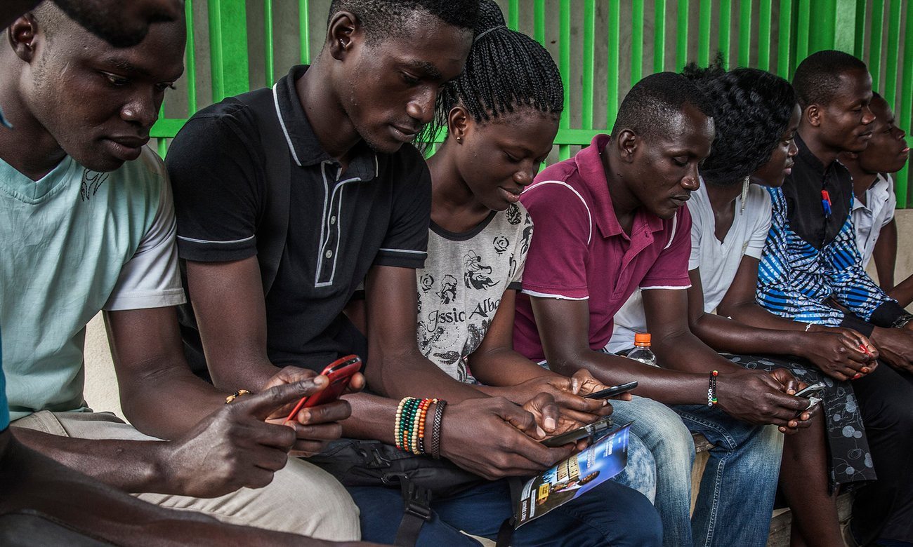Travellers consult their mobile phones in Abidjan, Ivory Coast. The number of smartphones in Africa is set to triple over the next five years Photograph: Bloomberg/Bloomberg via Getty Images