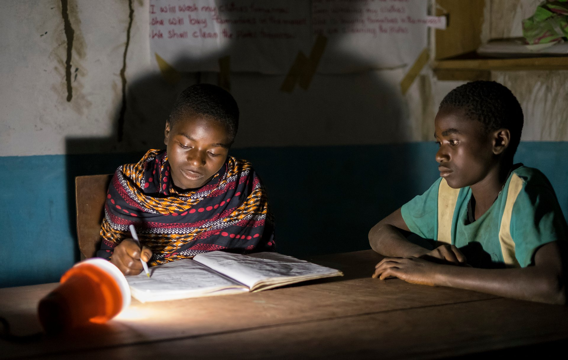 Pupils prepare for exams at night, using solar lamps, in Gumbi library