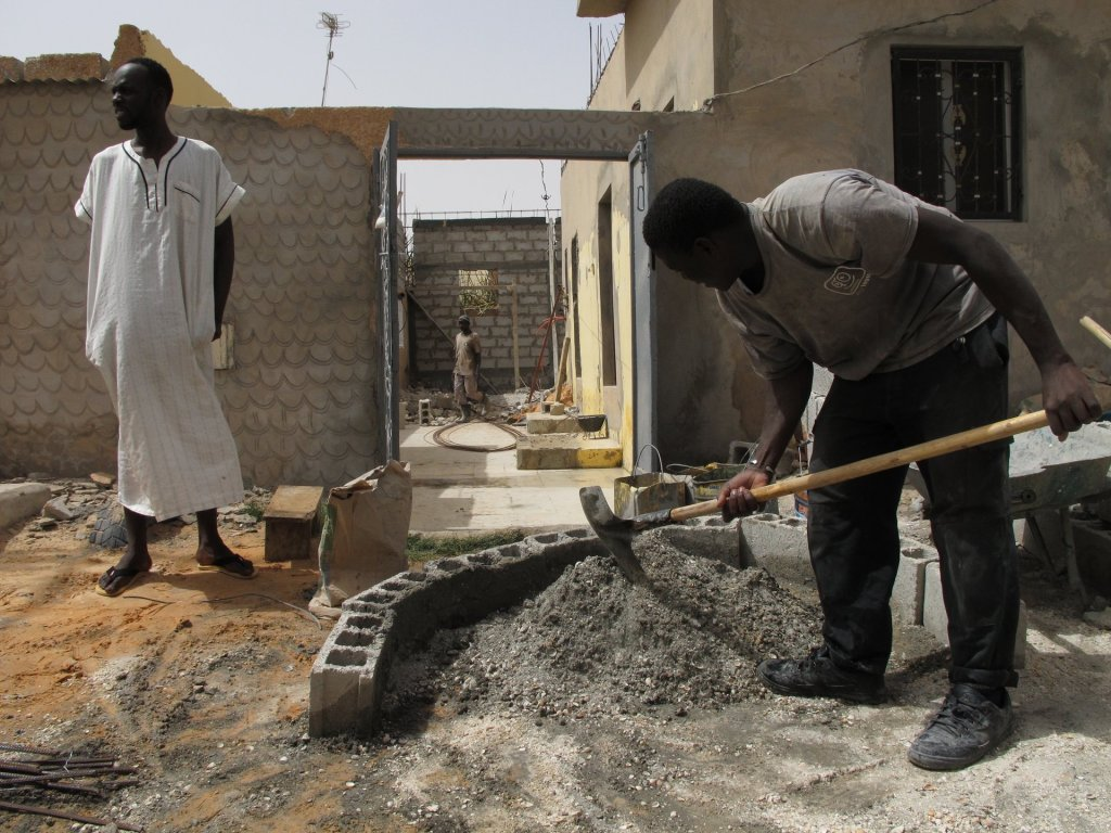 Vieux Fall, left, stands in the family compound in Nouakchott, Mauritania, as builders work. Photograph: Alex Duval Smith