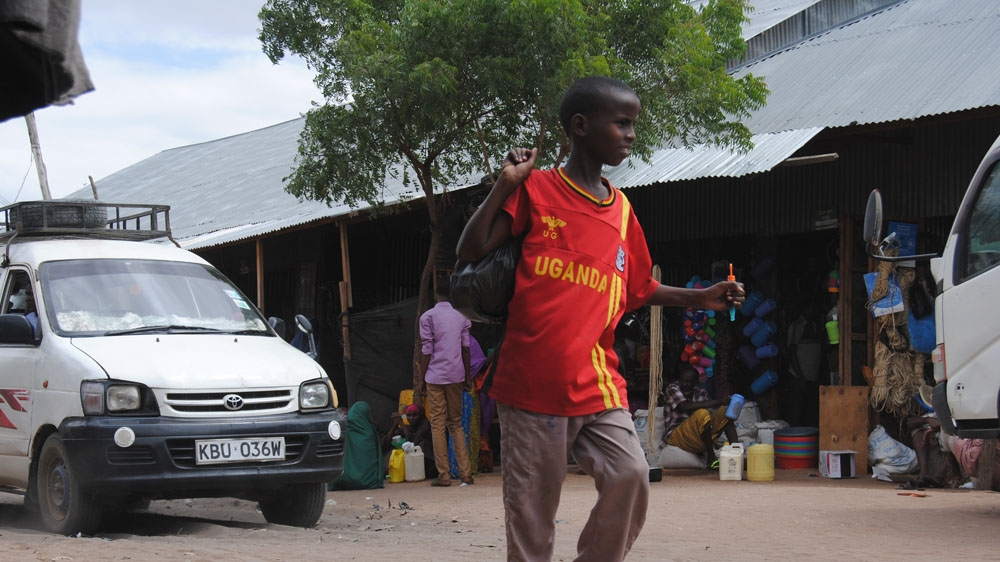 A young boy leaves the market place at Hagadera camp in Dadaab [Anthony Langat/Al Jazeera]