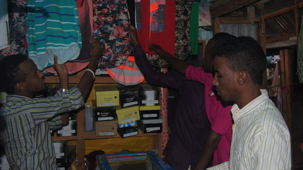 Deck Yusuf Mohamed, left, attends to customers at his family's shop in Ifo refugee camp [Anthony Langat/Al Jazeera]