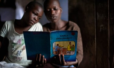 Young women read an educational book at an adolescent youth centre in Uganda. The government has pledged to inject up to $5m a year into family planning. Photograph: Neil Thomas/Getty Images