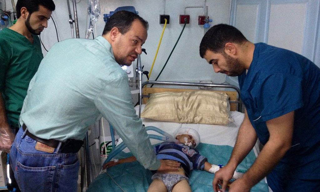 Dr Zaher Sahloul (left, front) treats a child casualty in a Syrian hospital Photograph: Handout