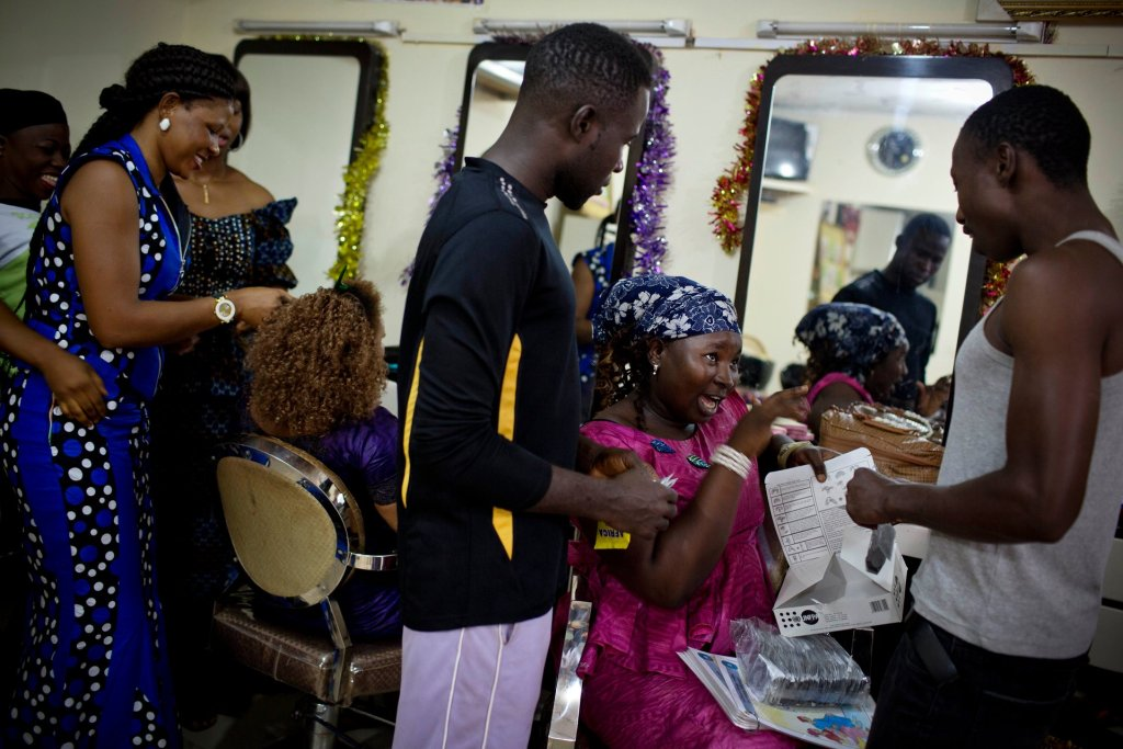 Young men who have come to Miskaa Salon for cut price condoms are shown how to use them correctly by apprentice hairdresser Nene Diakité. Photograph: Kate Holt
