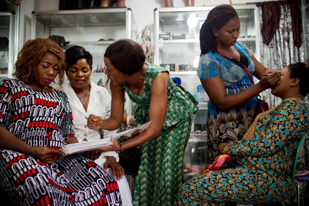 An apprentice hairdresser at the Jumelle salon in Conakry shows a client different family planning methods. Photograph: Kate Holt