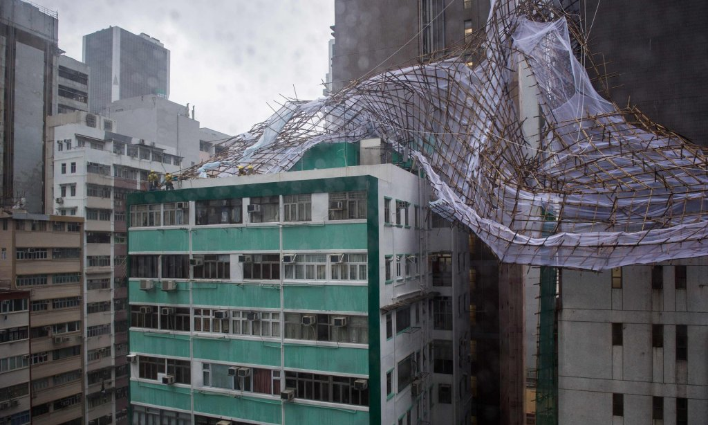 Rescue workers attempt to secure bamboo scaffolding that was damaged overnight at the top of a building in Hong Kong during Typhoon Nida. Photograph: Anthony Wallace/AFP/Getty Images