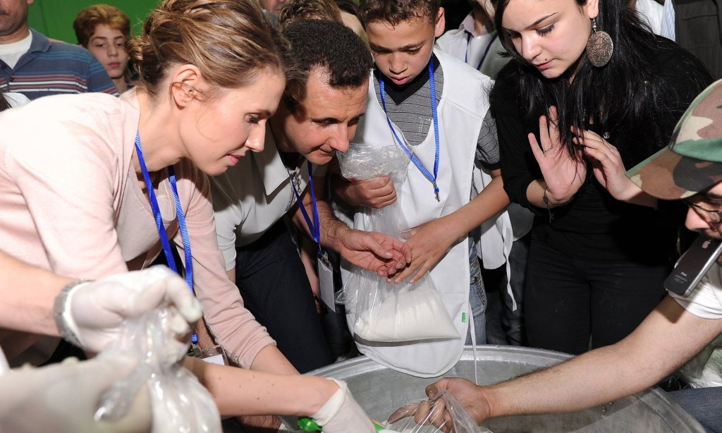 Bashar al-Assad and his wife, Asma, help pack aid supplies with volunteers at a food distribution centre in Damascus. Photograph: AFP
