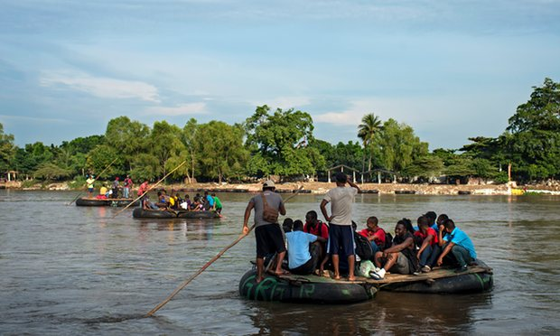 African and Haitian migrants cross the Suchiate river at the border between Guatemala and Mexico. Local rafters charge them eight times the normal rate. Photograph: Encarni Pindado for the Guardian