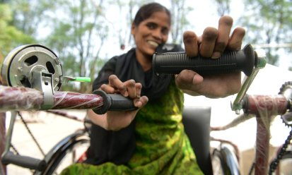 A woman smiles after receiving a mobility tricycle in Secunderabad, India. Photograph: Noah Seelam/AFP/Getty