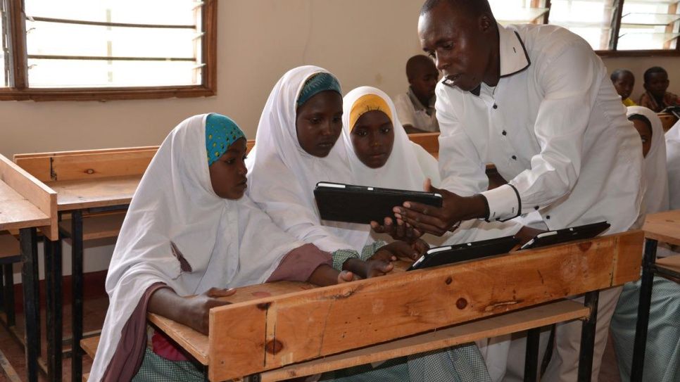Michael Mutinda, a teacher in one of the primary schools at Dadaab refugee camp in Kenya, shows his pupils how a tablet computer works, in this 2014 file photo. © UNHCR/ D.Mwancha