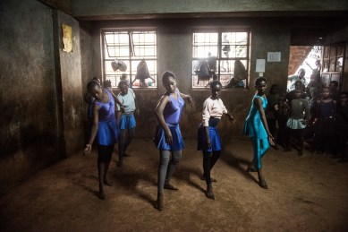 Some of the older girls is practicing a dance together, while the ballet class takes place there is always a whole group of curious students around the classroom/dance studio