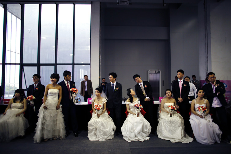 Couples wait to participate in a staged mass wedding, part of a matchmaking event to inspire singles to get married, Shanghai 2013. Carlos Barria/Reuters