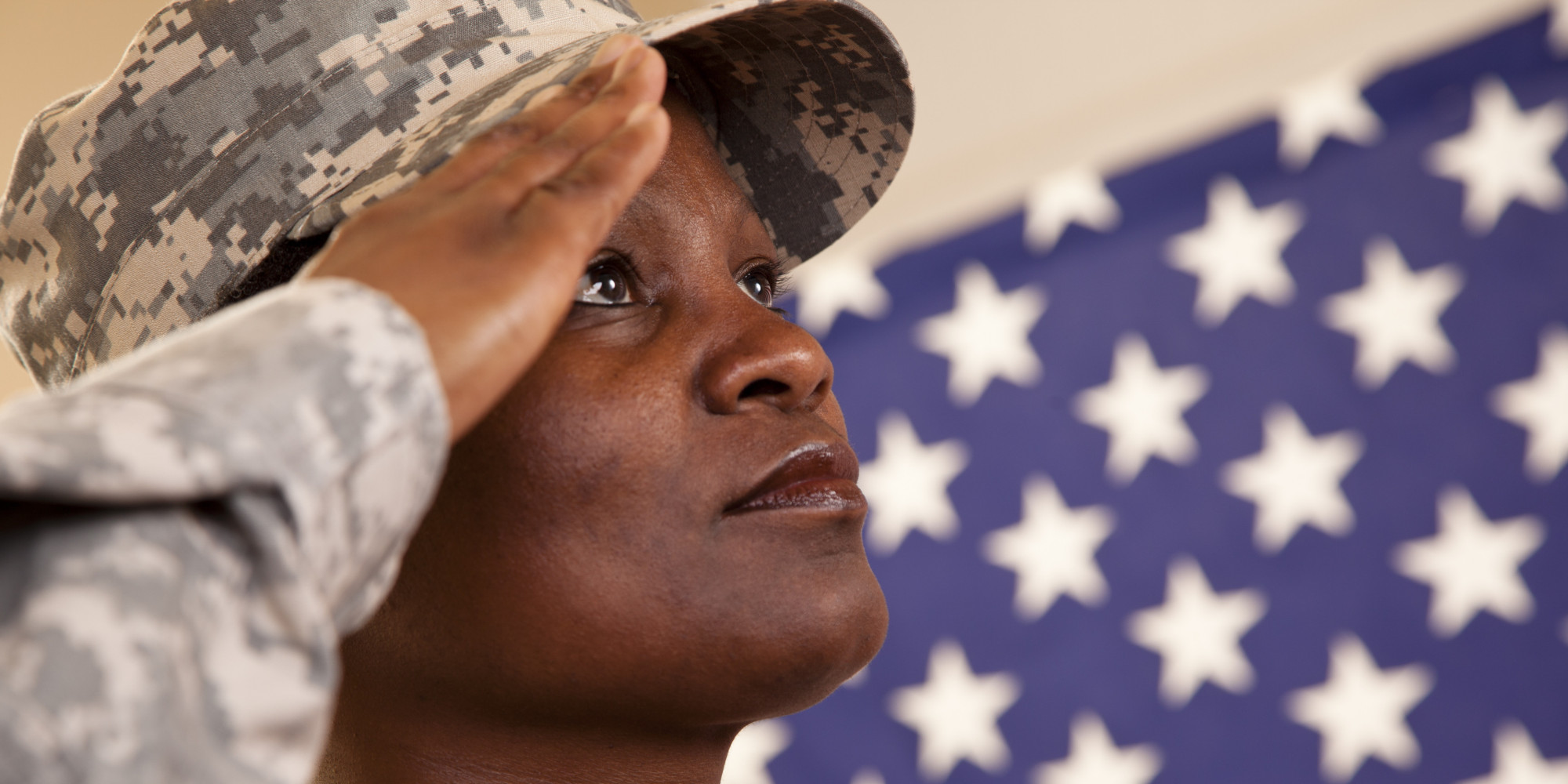 Patriotism: African descent military woman salutes American flag.