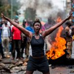 An opposition supporter in front of a burning barricade in Nairobi on Oct. 26. Photographer: Luis Tato/AFP via Getty Images