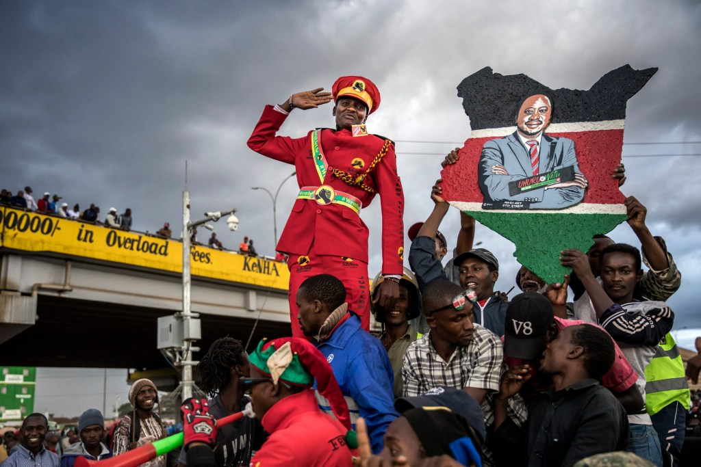 A supporter of Kenya's president Uhuru Kenyatta salutes from a crowd in Nairobi on Monday, Oct. 23, 2017. Photographer: Luis Tato/Bloomberg