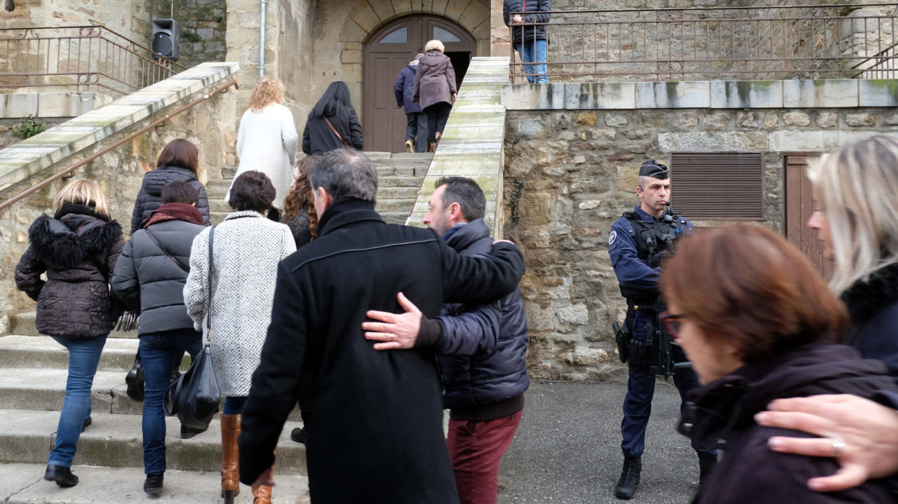 Mourners arrive at the Saint Etienne Church in Trebes in southwest France for a service of remembrance on March 25, 2018, two days after a man carried out an attack in which four people were killed. Mourners in this rural French town rocked by a deadly Islamist attack held a mass on Palm Sunday to pay tribute to the victims, including a policeman hailed a hero for offering himself in place of a hostage. Lieutenant-Colonel Arnaud Beltrame, 44, was shot and stabbed after taking the place of a woman whom Radouane Lakdim had been using as a human shield during his attack Friday on a supermarket in the small town of Trebes. / AFP PHOTO / Eric CABANIS