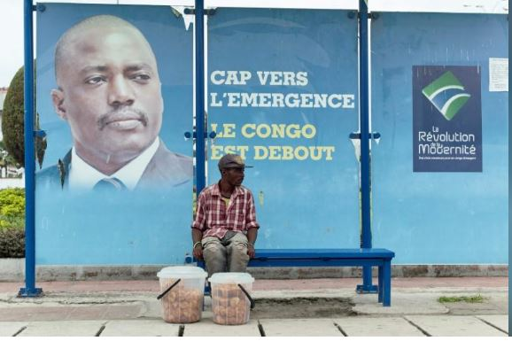 A vendor sits at a bus stand with pictures of President Joseph Kabila in Kinshasa, Democratic Republic of Congo December 31, 2016. REUTERS/Robert Carrubba