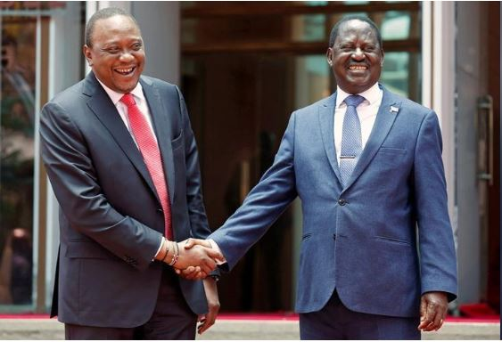 Kenya's President Uhuru Kenyatta (L) greets opposition leader Raila Odinga of the National Super Alliance (NASA) coalition after addressing a news conference at the Harambee house office in Nairobi, Kenya March 9, 2018. REUTERS/Thomas Mukoya